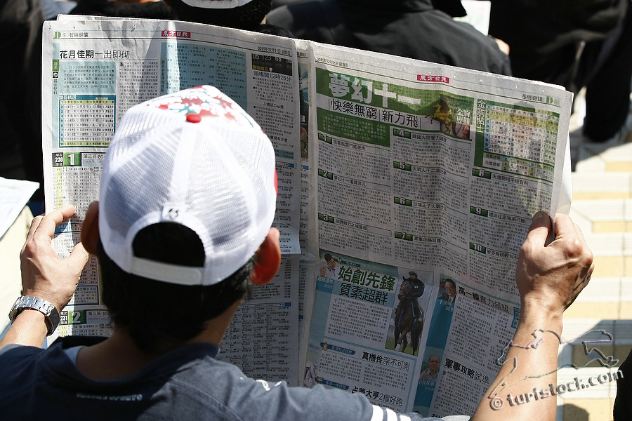 11. Dec. 2011 - Sha Tin Racecourse; Impressions: Racegoer read the racecard at Sha Tin Racecourse. Credit: Lajos-Eric Balogh/turfstock.com